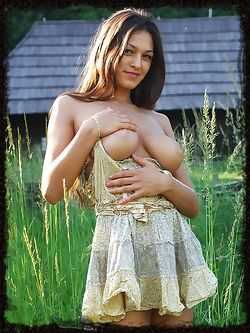 Sofi A teases her amazing breasts out of her little dress in a field of beautiful green grass.