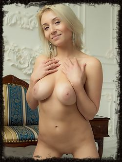 Pretty blonde Isabella D playfully poses naked for the camera highlighting her magnificent breasts and smooth legs