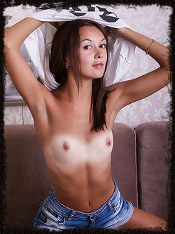 Veselin bares her slender, tanned body on the sofa.